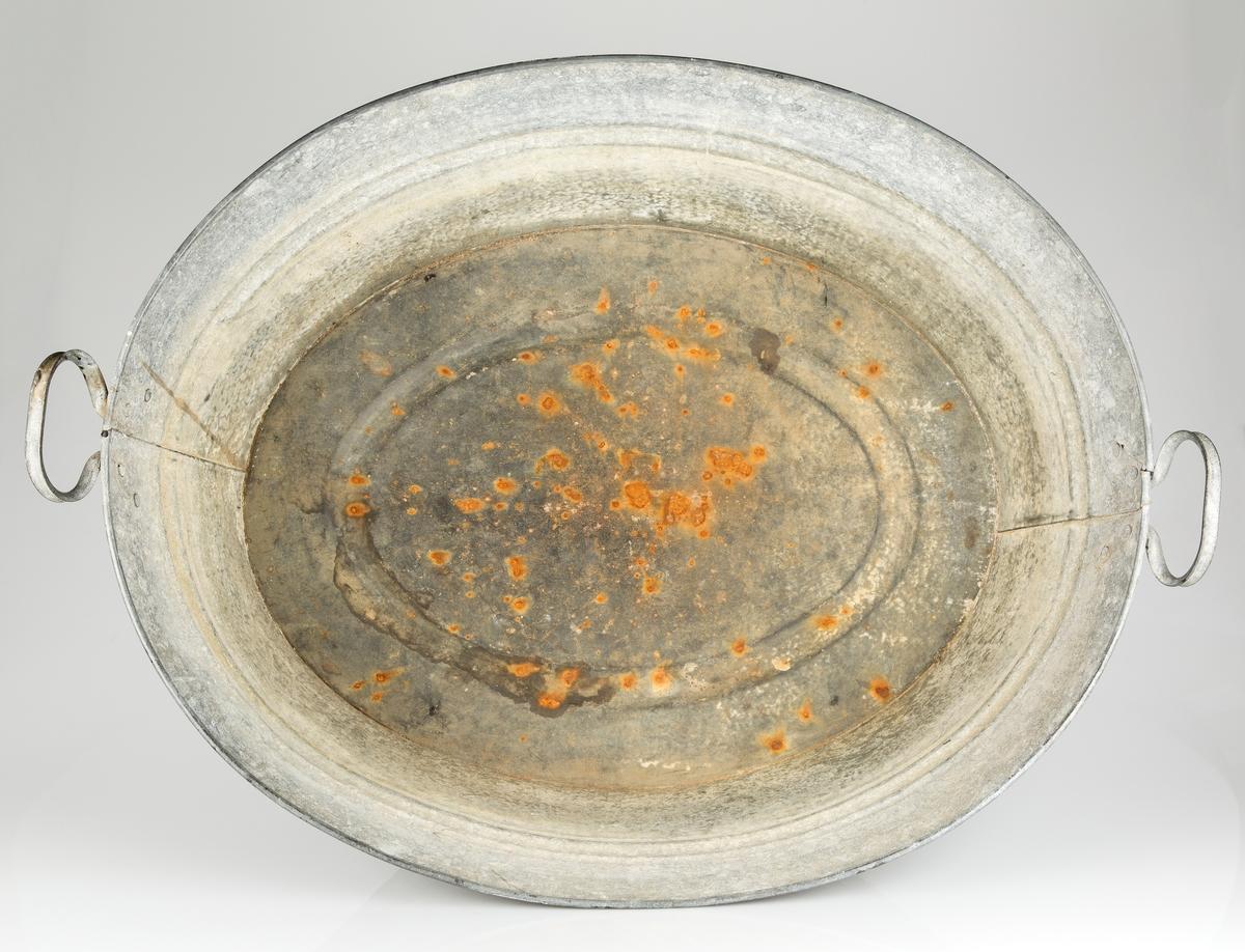 Oval sinkbalje med håndtak i hver ende. Lenger og bredere øverst.