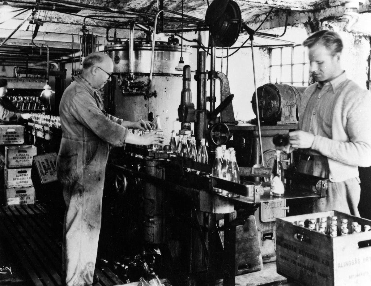 Bild på en kvinna samt två män som står i den gamla tappningshallen och arbetar vid det löpande bandet med flaskor. Från vänster: Brita Samuelsson, Nyman och okänd man. Bilden tagen innan Alingsås Bryggeri moderniserades på 1950-talet.