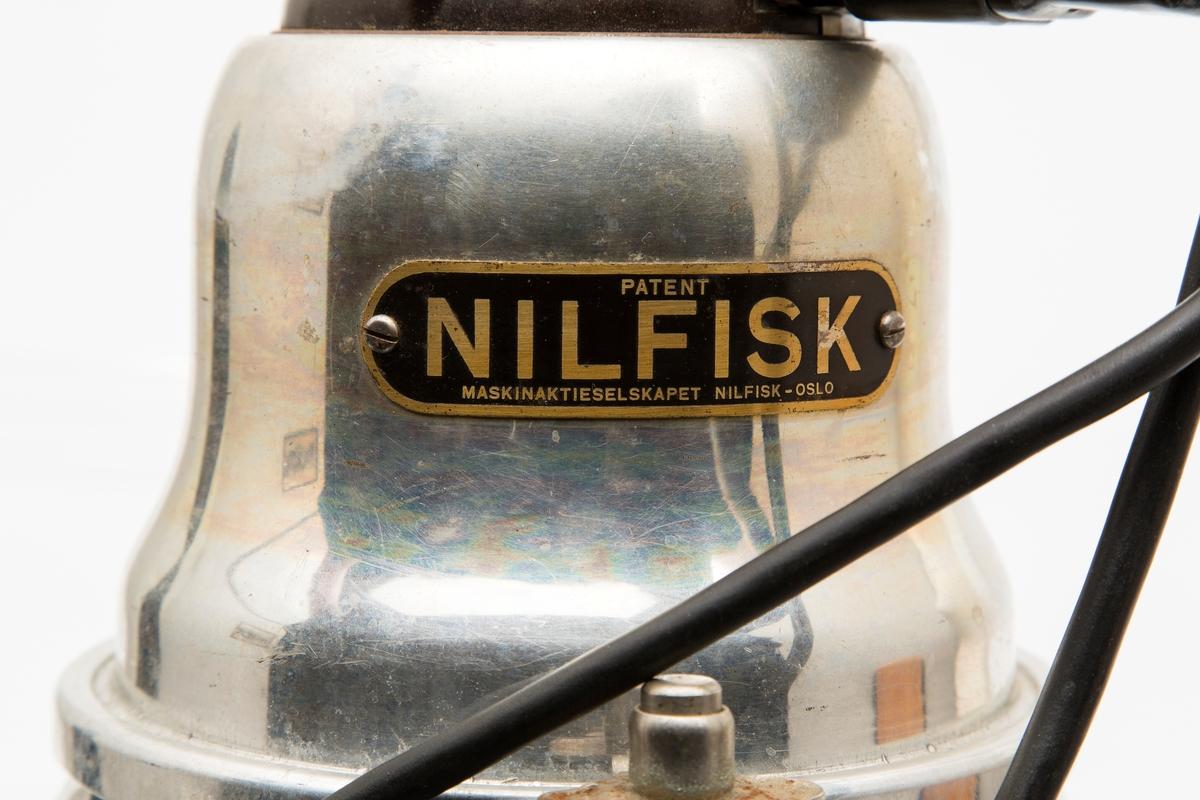 Høy, rund og flaskeformet støvsuger. Avsmalende øverst, understell med tre hjul, håndtak på toppen. Har tilbehør som støvsugerslange,, munnstykke og skjøtestang. Samt ministøvsuger med ledning som kan kobles på strømkabelen til hovedenheten.