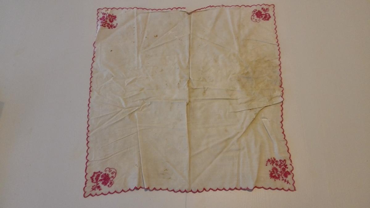 1 bordserviett  Bordserviett av hvit silke. Tunget kanter sydd med rød silke. I hvert hjørne sydd med rød silke et blomsterarrangement. 45,5 x 47,5 cm.
