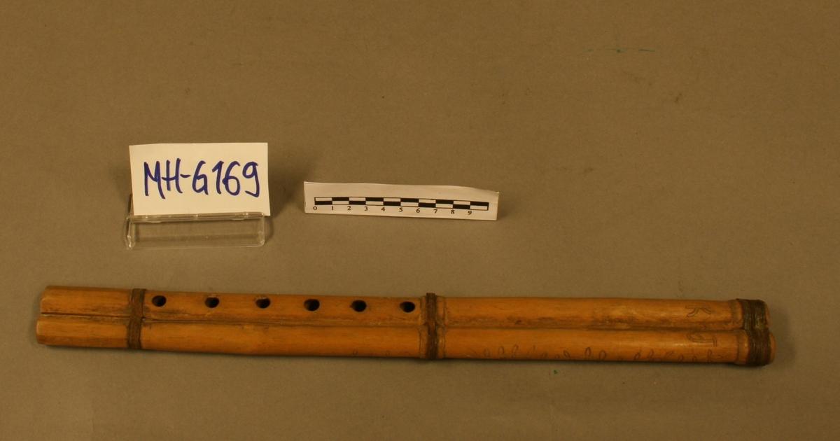 Dobbel spaltefløyte, uten nebb, med spalte og labium på undersiden. 2 individuelle like lange, sylindriske rør bundet sammen på 3 steder med metalltråd. Sett fra utøveren har det høyre rør 6 fingerhull på oversiden, uten tommelhull, ved fingerhullene er risset inn 1922 R i rektangulær ramme. Det venstre rør uten hull, dekorert med innrisset bladgren. Høyre og venstre rør ved spaltene merket henholdsvis k J. Begge rør ved foten oktogonalt omriss. Grunntone melodifløyte: g'. Total lengde: 40,1. Diameter ved foten: 1,05. Svingende luftsøyle: 37,5. Bordunfløytas spalte sprukket og labiet skadet. Prof. Gurvins liste: nr. 206.