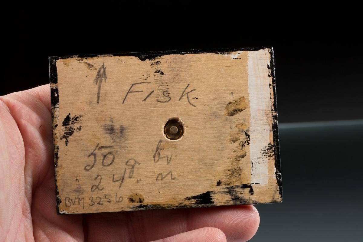 """""""Fisk"""" på svart plate med påskrift: """"Fisk, 50 g br, 24 g n, BVM 3256"""" Vekt: 49,66 g (med sokkel) Størrelse: 4,3 x 1,8 x 1,3 cm"""