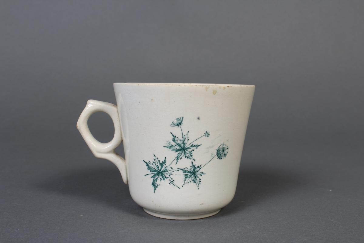 Kvit kopp med blått blomstermønster.