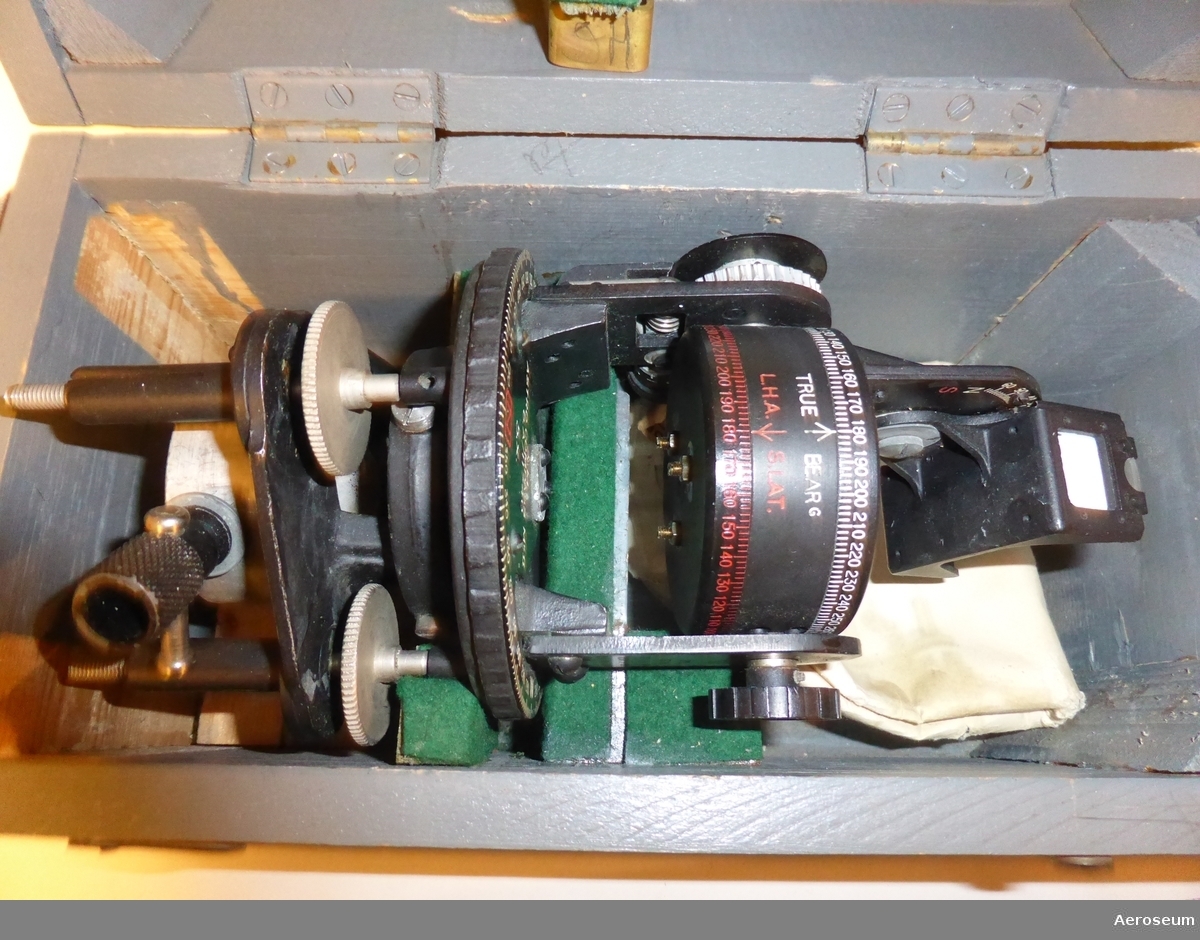 """en Astrokompass i en grå trälåda. Serienummer är 11592. På lådan går det att läsa """"ASTRO COMPASS MKII"""". På locket, lådans framsida och baksida står det med röda bokstäver och vit bakgrund """"DELICATE INSTRUMENT TO BE HANDLED WITH GREAT CARE"""".  På insidan av locket finns det en stämpel som ger årtalet 1944 och en papperslapp där det står: """"PACKING"""" och """"SET COURSE TO """"S"""" AND LAT. TO """"9"""" AND PLACE IN BOX WITH LEVELS DOWN""""."""