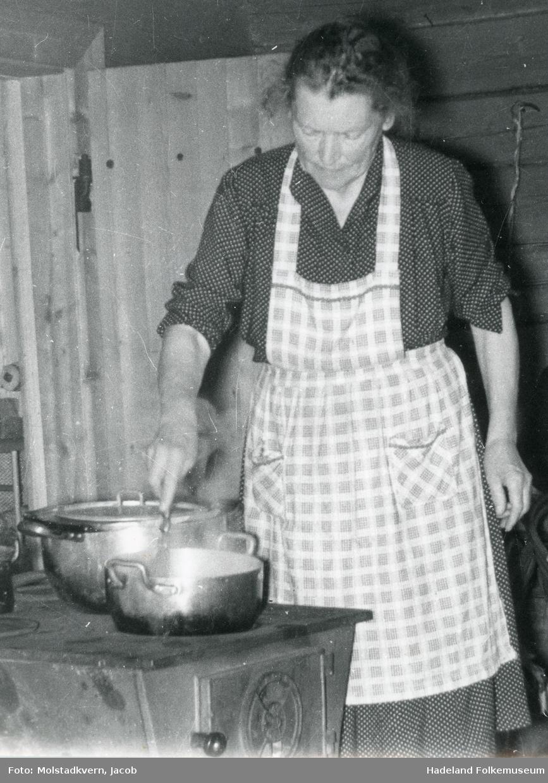 Kvinne med forkle står ved en ovn og rører i en kjele.
