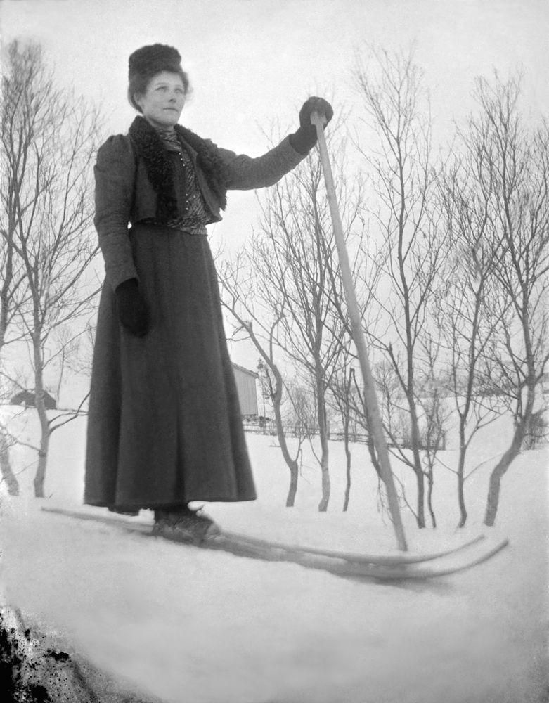 Leirfjord. Vinterbilde. Dame i skjørt og hatt på ski m/ en stav. Bildet er brukt i Leirfjordkalenderen - april 2014