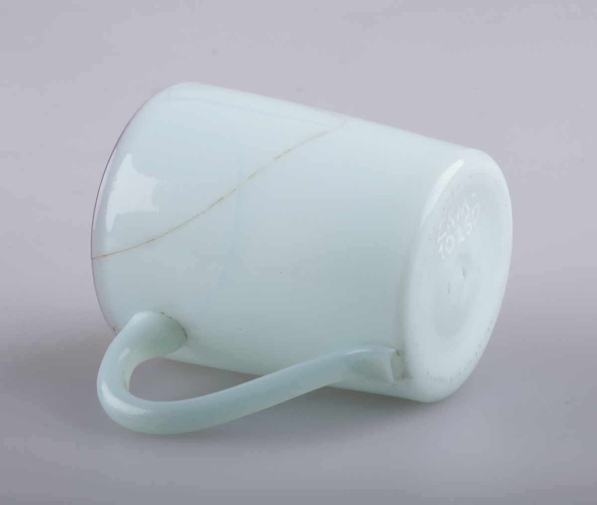 Punsjkopp i beinhvitt glass med brun ring. Hanken er i blankt glass, med hvitt glassbelegg rundt. Brutt pontemerke/puntelmerke under. Punsjen ble servert varm, og ble derfor drukket av små glasskopper med hank. Antagelig produsert på Gjøvik Glassverk (1807-1843).