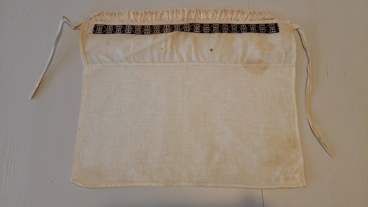 1 hyllik.  Hyllik, 30 x 24 cm. Har överst en kant svart saum i sort silke og er kantet med en rynket blonde.  Gave fra Fredrikke F. og Ole Gunnarsen Nesse, Ytre Kvamsö.