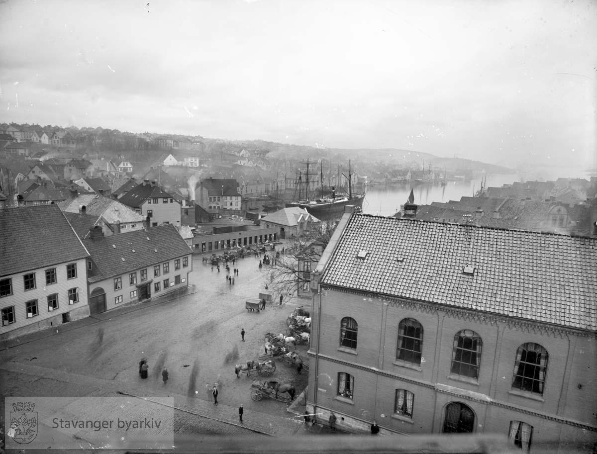 Til venstre: Byfogd Christensens hus og Svaneapoteket. Til høyre: Fengselet..Jernbanens godsterminal samt utsalgsboder midt i bildet..Seilskuter i Vågen.