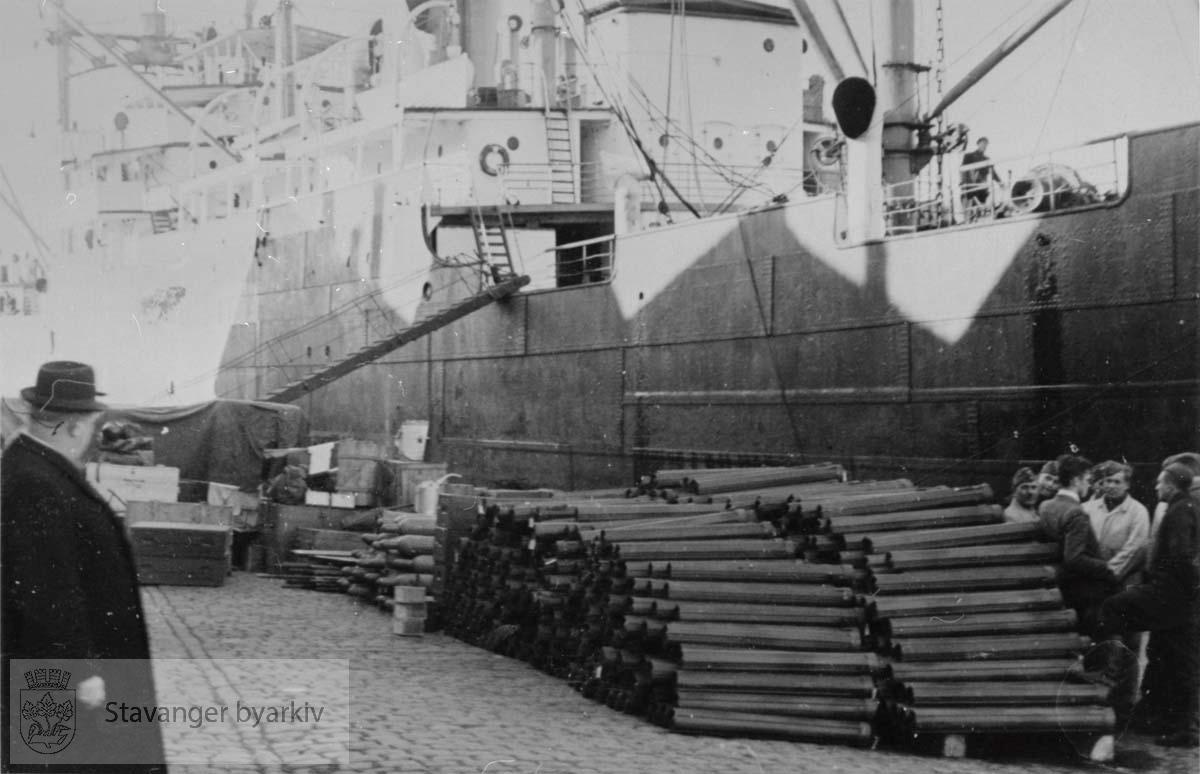 Lastebåt og militært materiell ved kaien