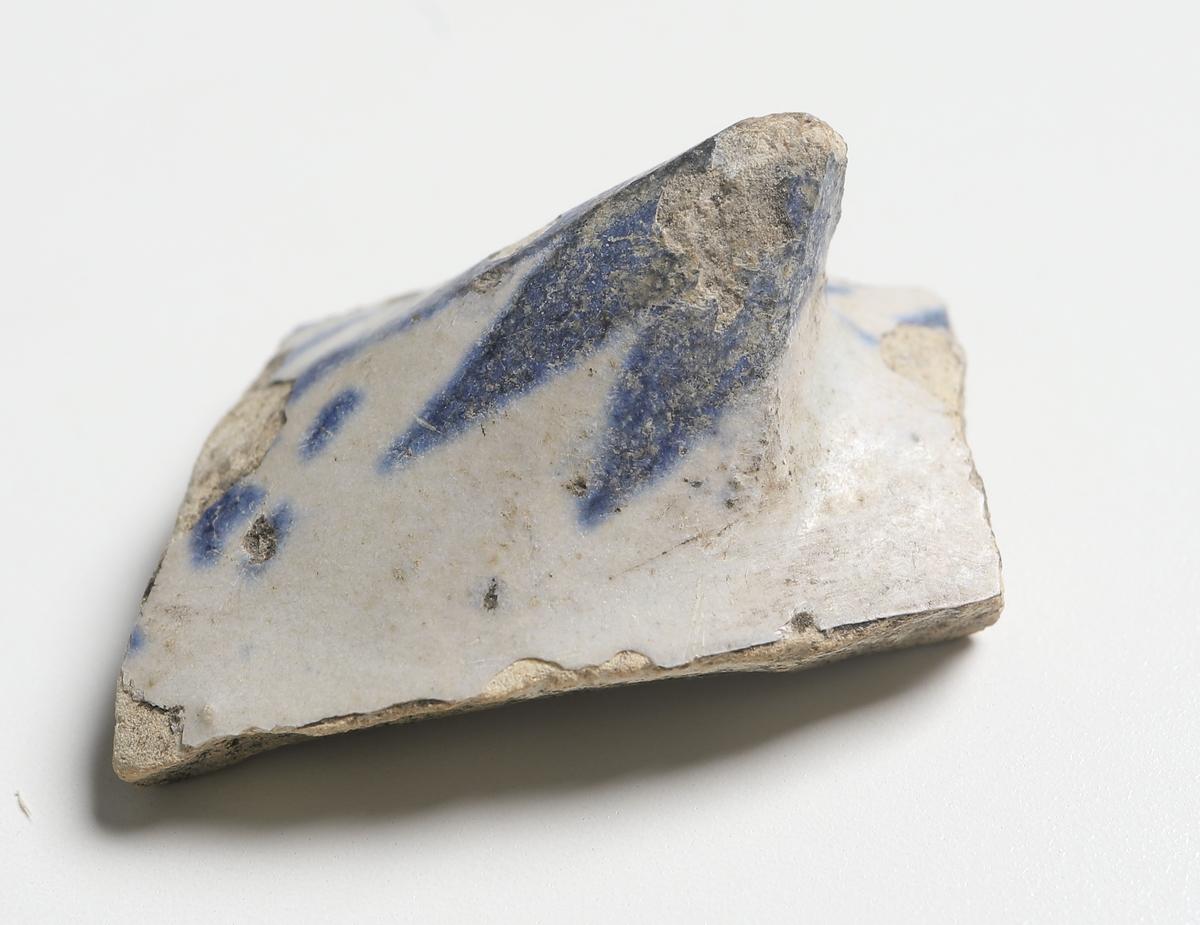 Bukbit av stengodskärl med vit ytterglasyr och blå dekor. Vitgrå glasyr på skärvans insida.