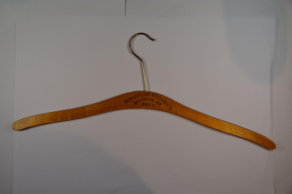 Enkel, buet kleshengere av tre med krok av metall. Benyttet i Bernsteins Magasin A/S, Markveien 67, Oslo.