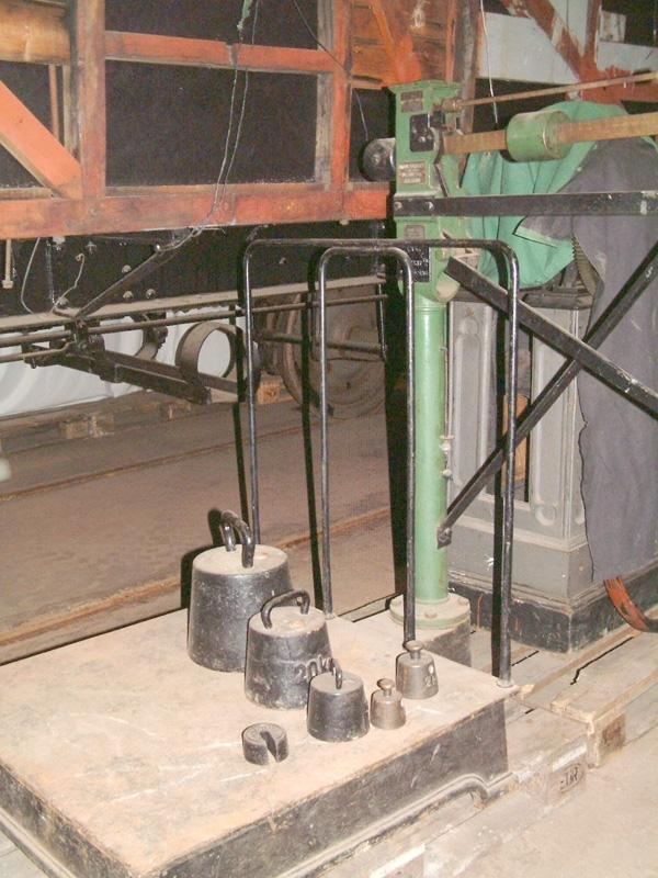 """Godsvåg med stativ av delvis grönmålat järn. Kvadratisk vågplatta av järn. Tillhörande vikter i gjutjärn med handtag med följande tyngder: 50 kg (:2), 20 kg (:3), 5 kg (:4), 2 kg (:5), 1 kg (:6). Med vitmålade bokstäver står på stativet: """"Avgiftsvåg"""". På metallskyltar står namnet på tillverkaren: """" Lindells vågfabriksaktiebolag, HB 500 kr., Jönköping"""", samt """"HR Lindells patent"""", och namn på återförsäljaren: """"Mårten E Liander maskinaffär Stockholm""""."""