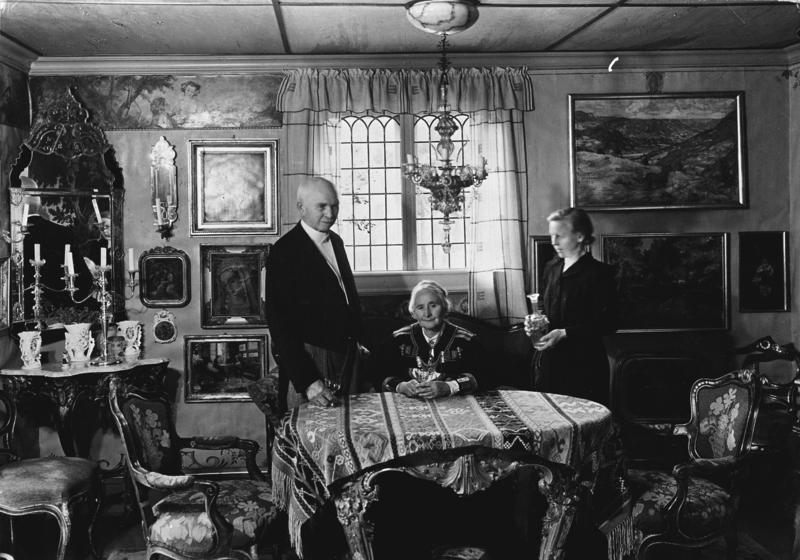 Otto, Tilla og Gundhild Bakke, deres tjenestepike, avbildet i Tillas stue i hovedhuset for Magasinet for Alle i 1962. Bordet og stolene i stuen er franske, mens lampen over spisebordet er av meronaglass fra Venezia, kjøpt i Firenze.