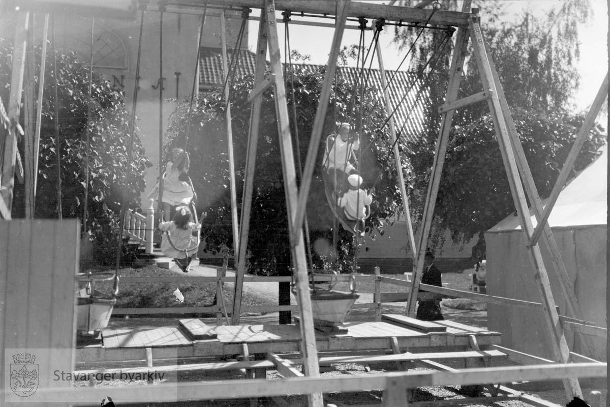 Barn i huskestativ. En kirke i bakgrunnen?.....NB! Dette fotografiet er sannsynligvis tatt av Hans Henriksen. Gard Paulsens og Hans Henriksens arkiver ble avlevert sammen. Sjansen er stor for at enkelte bilder har blitt blandet sammen.