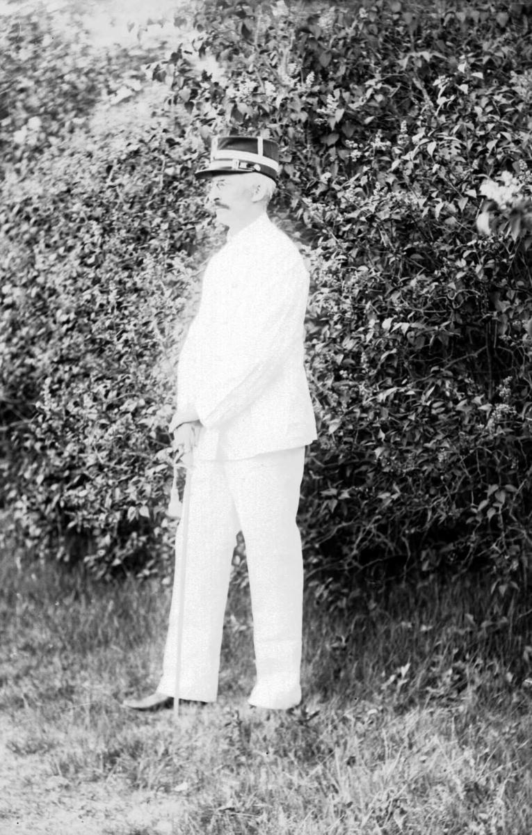 Portrett av mann i en hvit yrkesuniform fra hæren og uniformslue.