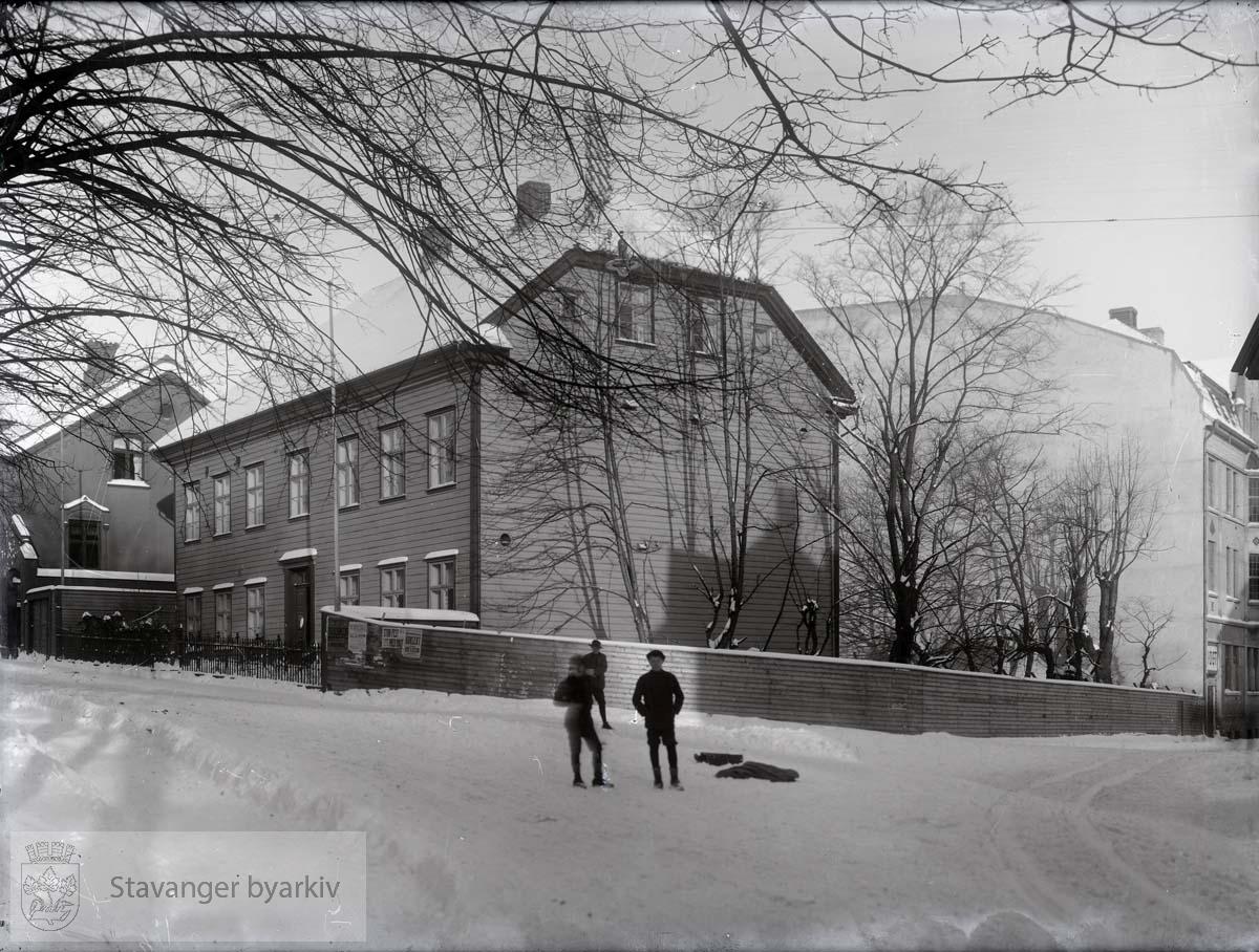 """Til venstre Laugmannsgt. 1, Norges bank, tidl. Ths. S. Falck. Til høyre Klubbhaven og I.O.G.T., Klubbgt...""""Allerede i 1837 hadde klubselskabet planer oppe om å opføre en bygning i Bispegårdens hage - Klubbhagen - for en sum av 3609 spd. 80 sk., men planen blev utsatt til 1841 og da vilde bygningen kostet 4000 spd. 26. november samme år foreligger en ny meget vidløftig kalkyle på 4 tettskrevne foliosider. Det gjelder nu en større bygning enn tidligere og til et samlet beløp av 5706 spd. 36 skill. Dimensjonene skal være 40 alen lang, 20 alen bred med to tømmeretasjer på gråstens kjelleretasje. Selve tømmerbygningen blir 13 alen høi fra grunntømmeret til gesimsen. Av beløpet var 20 spd. regnet for gatedøren med lås, hengsler, vindu over, trappesten og øvrige forsiringer..Det har ikke vært mulig å finne tiden når arbeidet er begynt, men 10. oktober 1843 optas takst over bygningen som da ikke var ferdig. Den manglet gulver, lofter, dører, vinduer og bordklædning. Dimensjoenen er nu 31 alen lang, 19 alen bred, 12 1/2 alen høi. Taksten blev 1440,0 spd. 26. mars 1845 avholdes ny takst. Nu er huset helt ferdig. Det inneholder 13 tømrede værelser, kjøkken og spiskammer, 3 tømrede ganger, muret kjeller med ildsted, 41 fag vinduer og 8 kakkelovner = 3610 spd. Ved bygningens østre ende står en toetasjes bindingsverk bygning med et gammelt værelse og et ditto skråkammer samt 3 fag vinduer, 5 1/2 alen høi, 12 alen lang og 7 1/2 alen bred = 80 spd. Et plankeverk 95 1/2 alen langt og 3 1/2 alen høit som inneslutter hagen fra gaten = 70 spd. tilsammen 3760 spd., et temmelig avvigende tall fra kalkylen og man må efter dette kunne gå ut fra at det er den første plan der er kommet til endelig utførelse. Senere blev der bygget kjeglebane og kjeglebanehus i hagen på nedre side av Skolebekken med to broer over denne.""""..Fra: Det Stavangerske Klubselskab og Stavanger by i 150 år. Stavanger 1934. Forfatter: Trygve Wyller."""