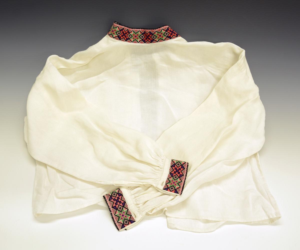 Modellbunad for Øst-Telemark TGM-BM.1999:0144.A-E B. Kvinneskjorte. Hvit skjorte med åpning fra halsen og helt ned. Ved åpningen er det sydd på et ekstra stykke smalt tøy på venstre side, for å skjule åpningen. Korsstingsbroderier foran på brystpartiet og på hals- og ermkvarder.