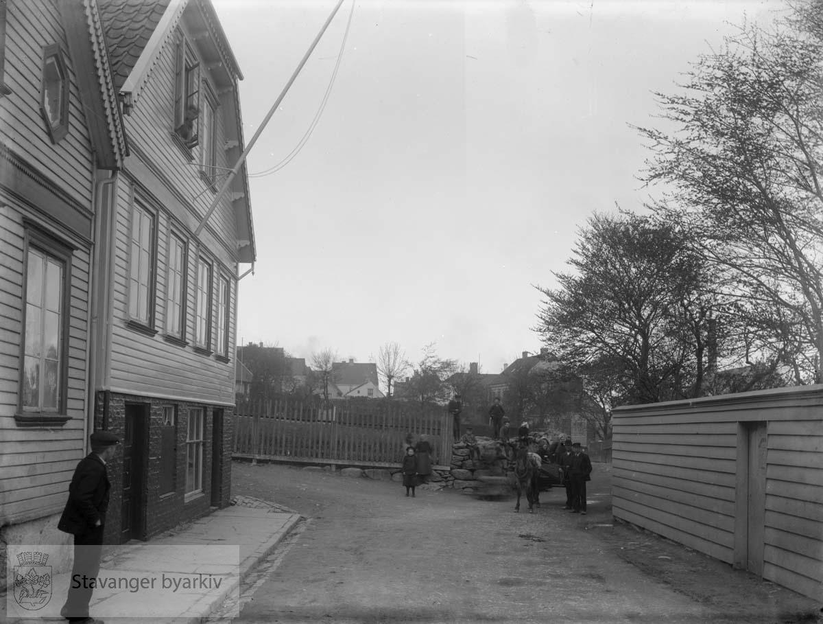 Til venstre: Øvre Strandgate 36 og 38. Hermetikkfirmaet Stavanger Preserving startet sin virksomhet i Øvre Strandgate 38 i 1873. Planke- og steingjerdet gjerder inn boktrykker Kiellands eiendom, Bergene. Øvre Strandgate smalner innover i bildet mot bebyggelsen på Straen. Mann med hest og kjerre, tilskuere.