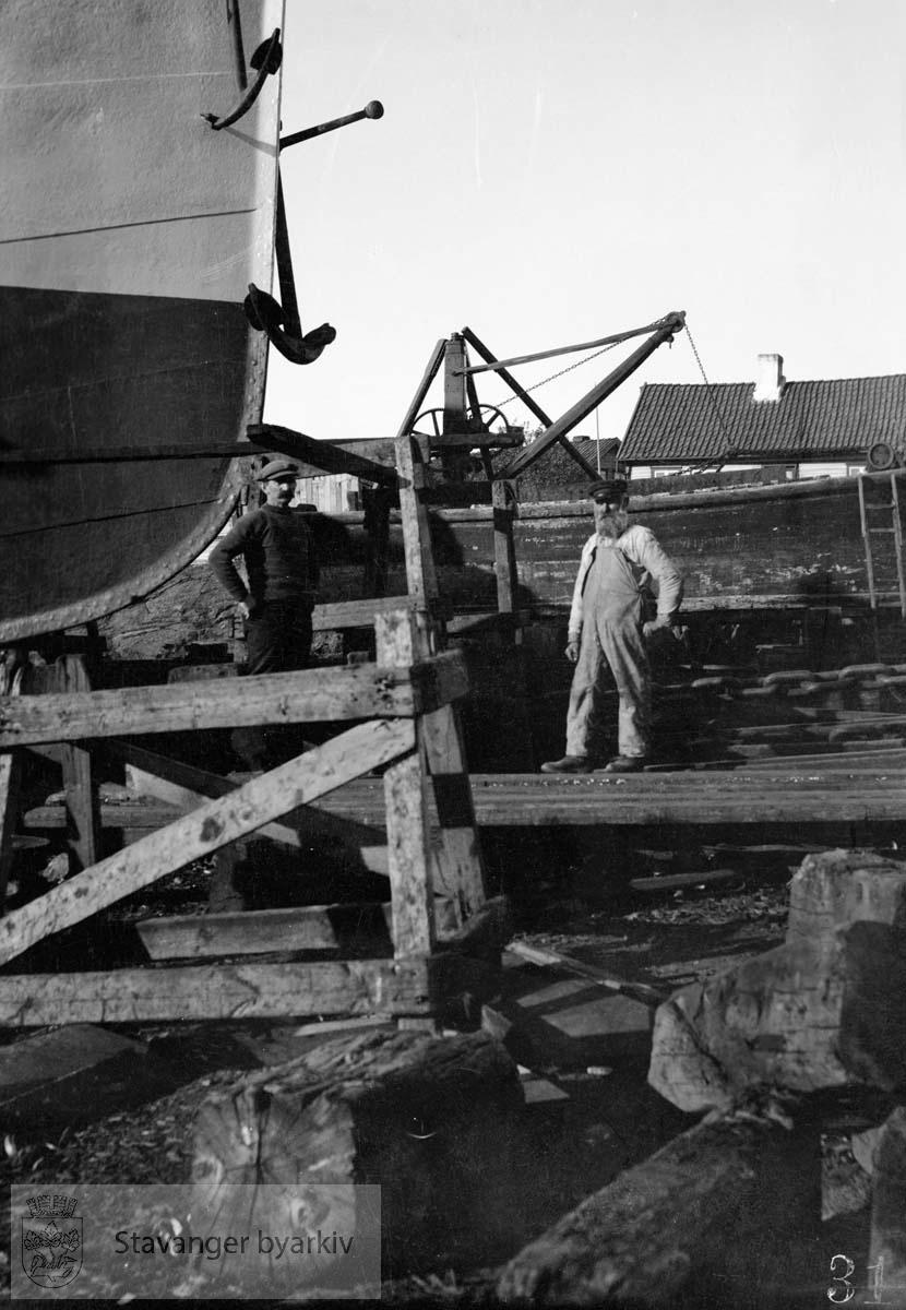 To mann ved skip i dokk, Buøy