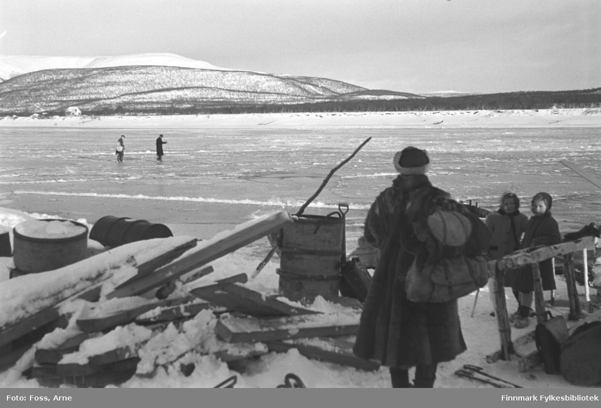 """Seida fergested, oktober 1946. To menn går over elva, isen har knapt lagt seg . To småjenter og en voksen venter ved stranden. """"Vannet er nesten bare issørpe, tidlig på dagen""""."""