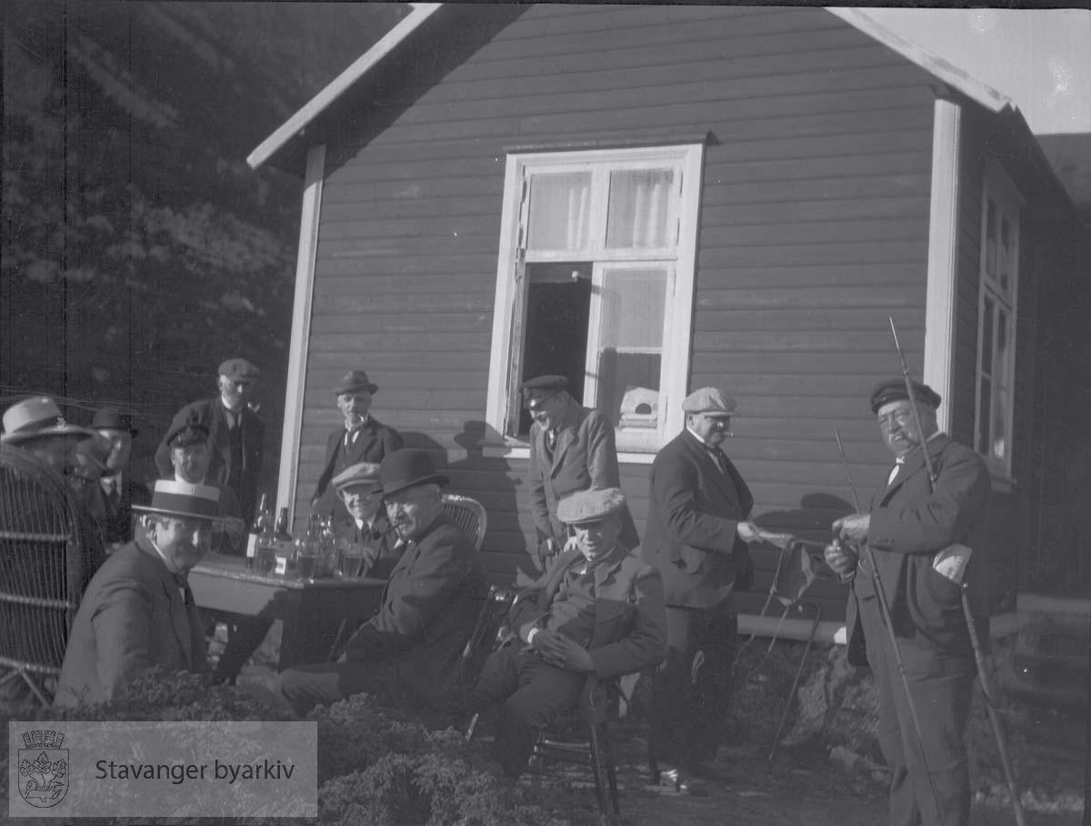 Menn utenfor med piper og fiskestang. ..Rosenberg Mekaniske Verksted
