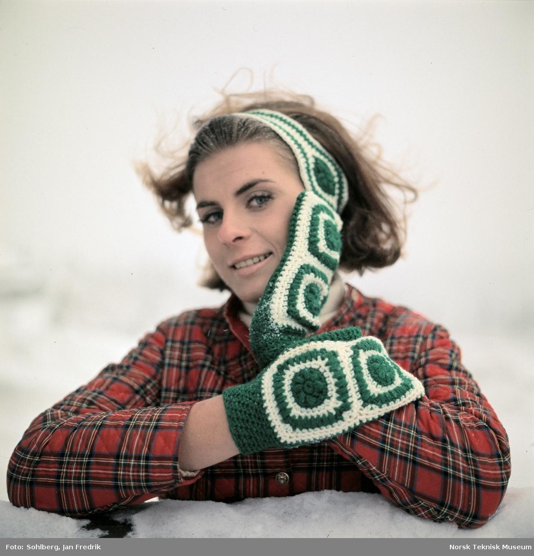 Kvinnelig modell viser vintermote. Hun har heklede votter og pannebånd av hvitt og grønt garn.