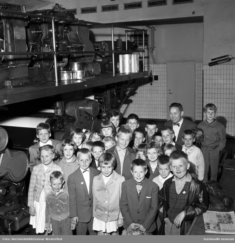 Studiebesök på Dagbladet. Gruppfoto av elever från Bybergets skola i Ånge invid den stora tryckpressen.