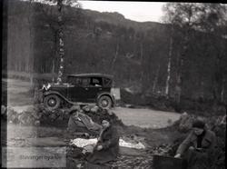 Bilen parkert og passasjererne sitter på tepper