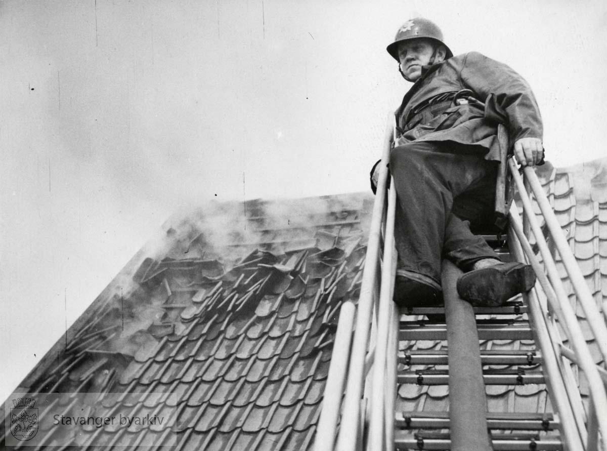 Brannmann M. Samuelsen ytterst på stige oppå taket til sjøhuset til D.S.D.