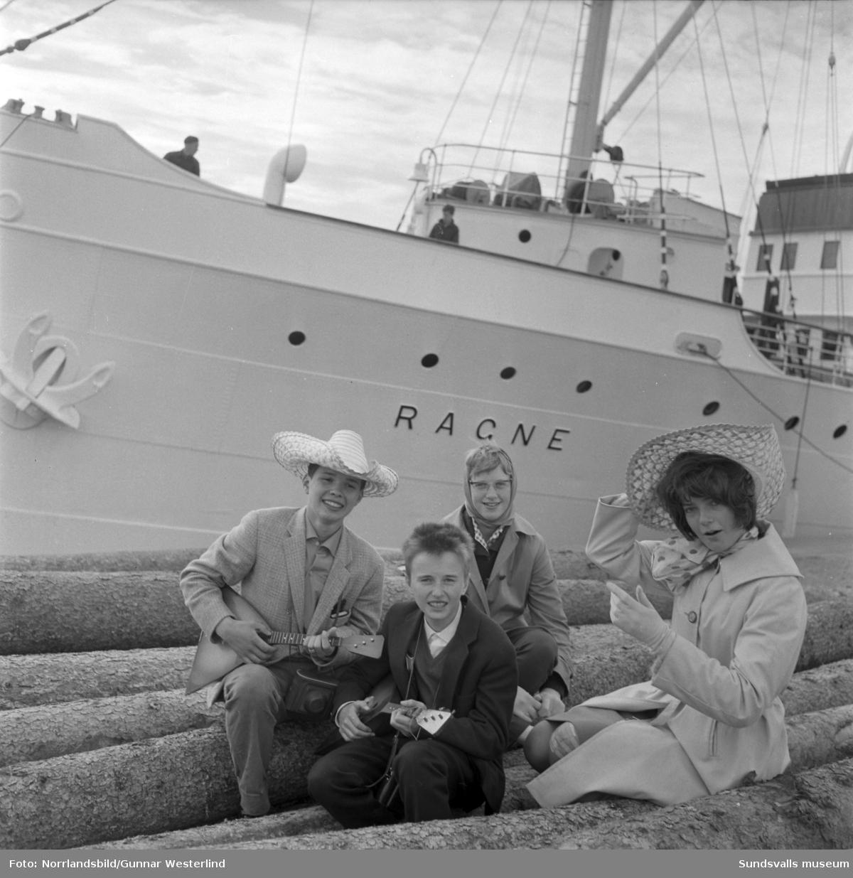 Skolklassen från Kyrkmons skola som varit på exotisk skolresa i österled återvänder med båten Ragne till kajen i Sundsvall och välkomnas av såväl media som familj och släkt. På första bilden är det radiomannen Bertil Hedlund som språkar med magister Gunnar Tjernberg. Resan hade gått från flygplatsen på Skeppsholmen till Vasa, vidare med tåg till Leningrad där fyra hela dagar tillbringades, tåg tillbaka till Helsingfors och sedan till den finska vänorten Ilmajoki. Några av eleverna på bilderna är: Ove Johansson, Maud Eriksson, Ann-Britt Pettersson, Ulla-May Nordin, Asbjörn Sjöö och Bror Hed.