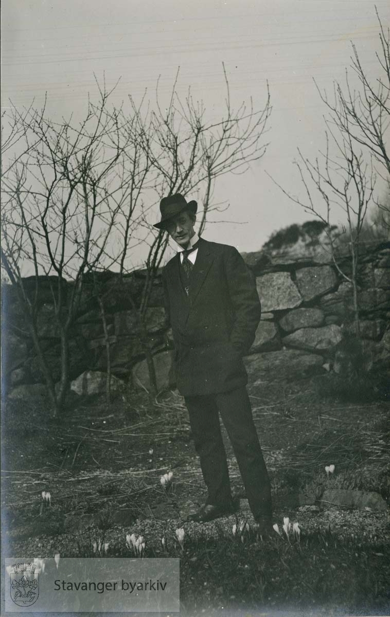 Helportrett av mann ved steingjerde.Likner på Hans Henriksen