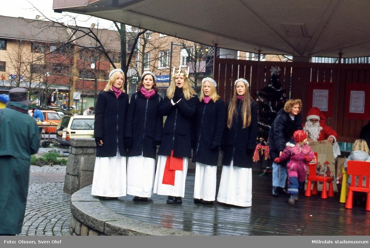 Lucian och hennes tärnor står på scenen vid Mölndals torg och sjunger, den 16/12 2000.