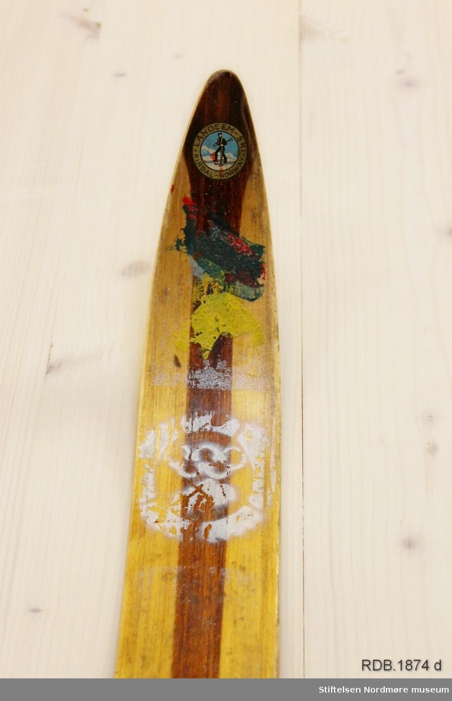 Avsmalende, jevnbred ski med liten bue. Bøy uten tupp. Rett avskåret bakende. Dekorert med ei brun stripe på trehvit bunn.  Noen stempel fra OL øverst på skiet.