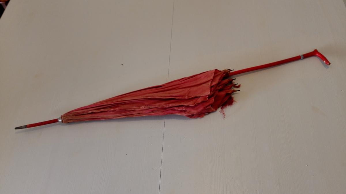 1 dameparaply.  Dameparaply, raudt trekk, metallspilar, skaft og handtak av trevyrke som er målt raudt. Trekket noko skadd. Lengd 92.5 cm. Kjem frå fam. Meidell, Balestrand.  Svein L. Vold