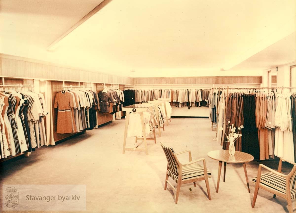 Norem Baades konfeksjonsavdeling i Kirkegaten, butikkinteriør, kjoler og drakter, kåper. Stoler og bord. Utskilt fra PA293.