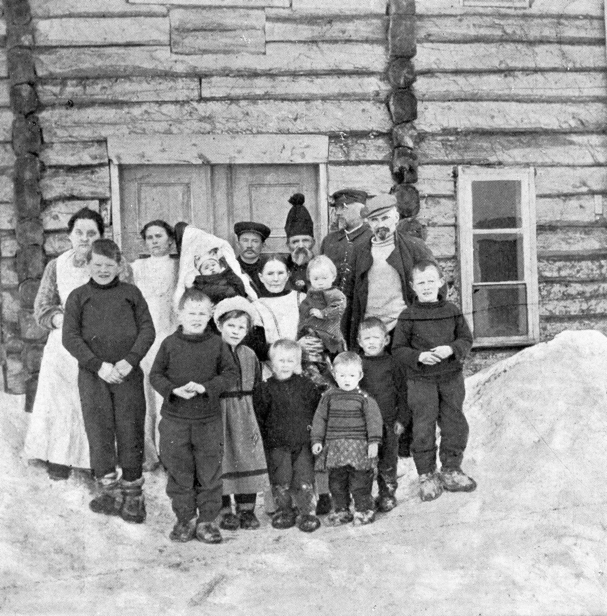 Barn og voksne, avbildet ved inngangspartiet til en stor tømmerbygning. Et lite barn i komse