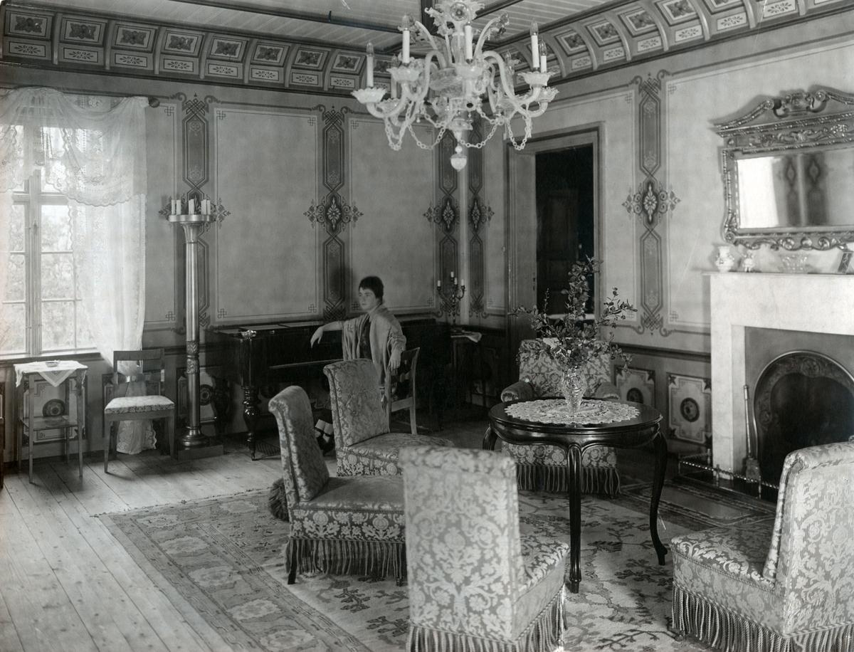 Bildet viser havestuen med åpen dør inn mot rødstuen. Victoria Bachke sitter ved taffelpianoet i enden av rommet.