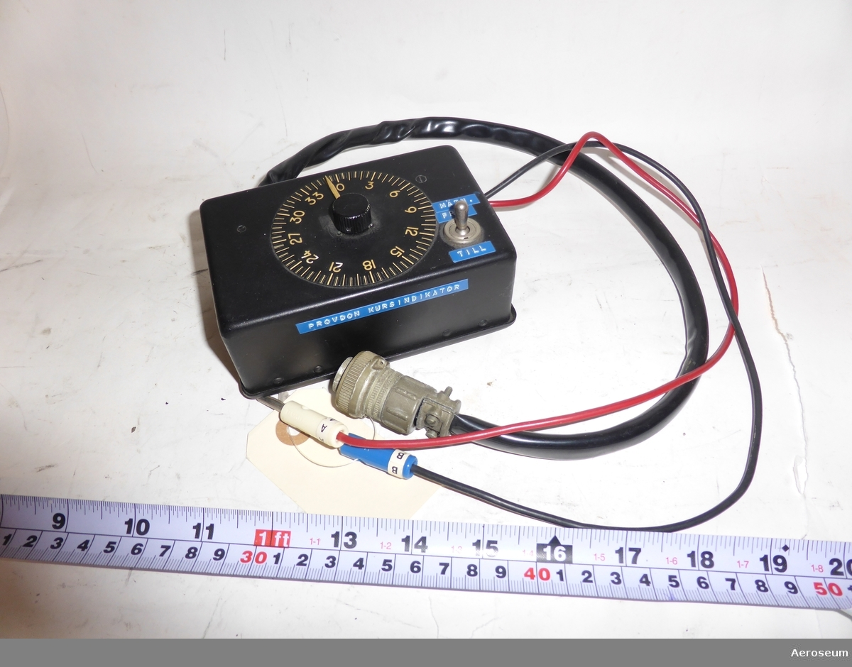 """Ett provdon för kursindikator i svart. Har en tjock svart kabel och två små sladdar, varav en i rött och en i svart. Märkt med dymoremsa """"PROVDON KURSINDIKATOR"""". Troligtvis ett hemmabygge, flera olika instrument har använts. Den graderade """"displayen"""" kommer från en """"Filotecnica Milan-Italy Gyro magnetic compass type V8"""". I botten av den fyrkantiga lådan står det: """"Control Unit type B.L. MKT Ferranti Ltd""""."""