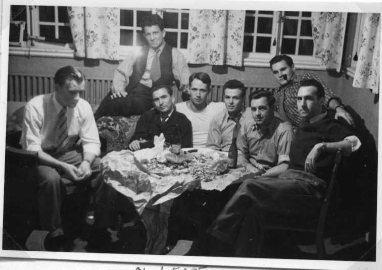Åtta män sitter i soffa, fåtölj och stol runt ett bord. Fyra från vänster i soffan är troligen Janeczek.