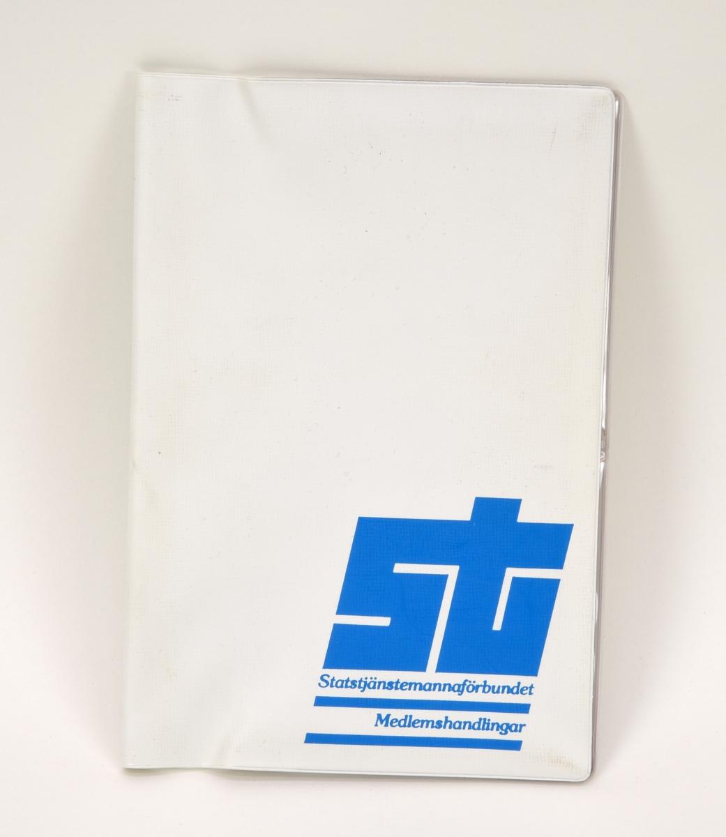 """Vit plastmapp med Statstjänstemannaförbundets logotyp och """"Medlemshandlingar"""" i blått tryck vid nedre högra hörnet. På insidan finns fickor i genomskinlig plast, på vänstra sidan två fickor i fullängd, på den högra finns likadan fickor men de är delade på mitten."""
