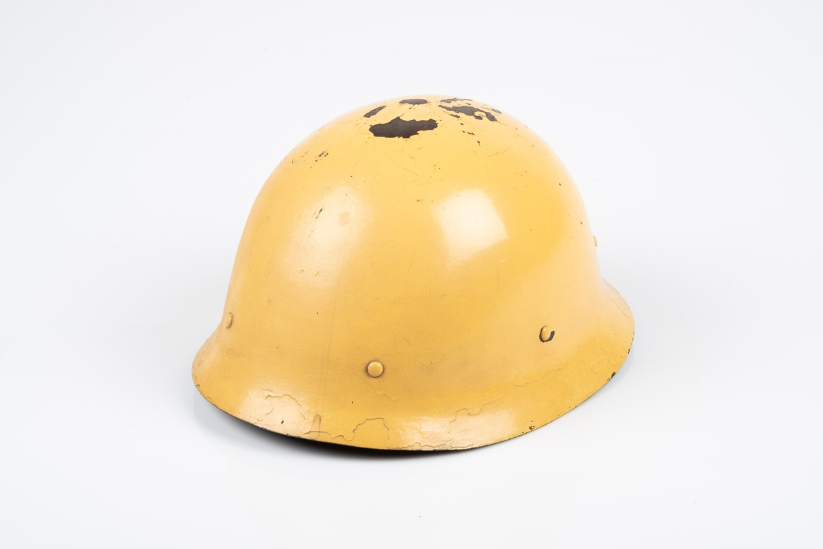 Tysk soldathjelm i metall. På innsiden er det festet en innerhjelm av lær med snor som brukes til å tilpasse hjelmen etter hodets størrelse. Hjelmen har lærrem med metallspenne. Hjelmen er malt gul på utsiden og brun-grønn på innsiden.