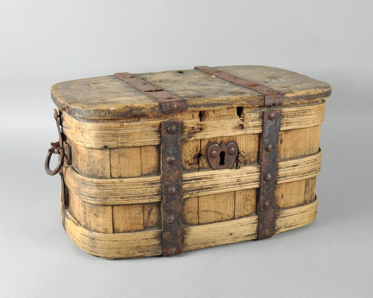 Skrin av tre som er avrundet i hjørnene. Skrinet er satt sammen med boltede jernplater, kan låses med nøkkel og har hanker på hver kortside.