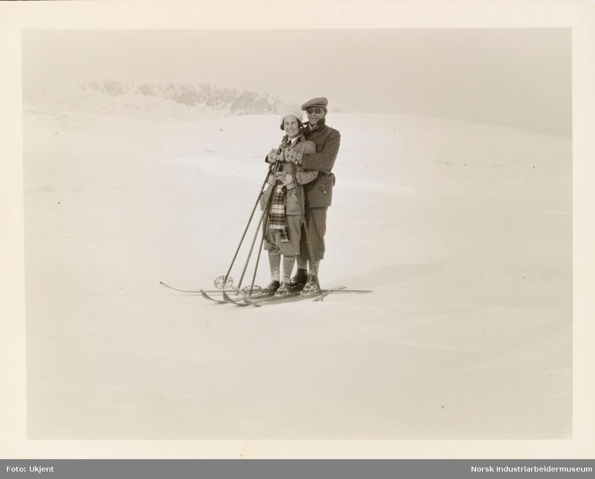 Mann og kvinne holder rundt hverandre på skitur i turantrekk, med ski og skistaver