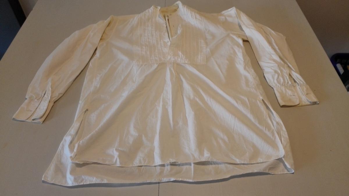 """Skjorte til fint bruk med handsydde  knapphol. Truleg ferdig kjøpt. Samansett av kvit poplin og bomullsstoff i ripsbinding. Berestykke. på skulder. Ryggstykke. rynka til berestykke. Framstykke glatt sydd til berestykket. Erme glatt sydd til bol. Lagde sidesaumar med splitt nest forsterka med liten kile øvst i splitten. Lagd ermesaum under. Dobbelt skjortebryst. 6 vertikale biser på venstre skjortebryst, 7 på høgre Doble mansjettar. 2 knapphol på kvar mansjett. 4 """"skilpadde""""-knappar i høgre skjortebryst."""