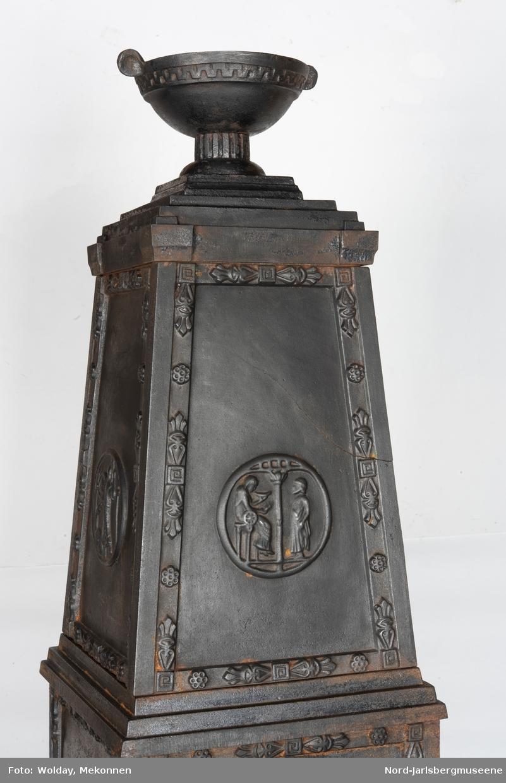 Høyreit, firkantet ovn med pyramidetopp. Urne på toppen. Toppstykket jar mdaljongdekor på alle fire sider med