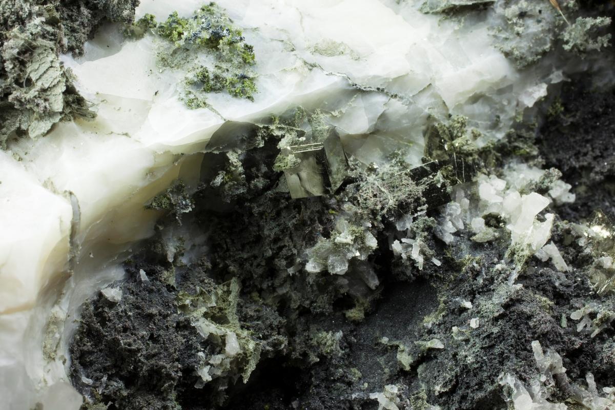 Svovelkis, kuber, skarpe, blanke, etset ut fra kalsitt. Kloritt, kalsitt, bergart, kvarts + sort. Bjønndalen Bruk