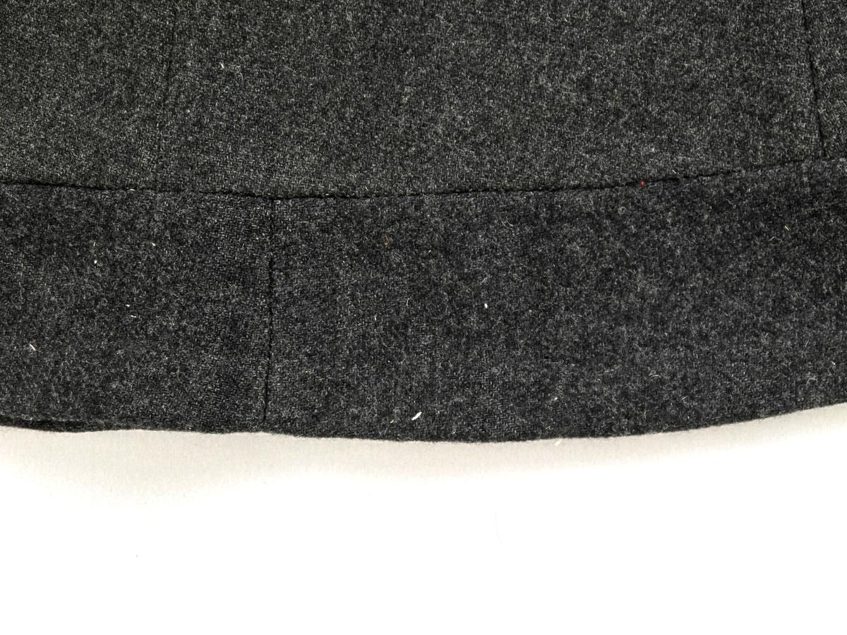 Skjørt. Ullstoff.  Koksgrå farge. To lommer og to hemper.  Glidelås. Trolig omsydd fra en mindre størrelse. Opprinnelig satt sammen av 6 trapesformede stykker, utvidet med et smalere stykke, og forlenget med 8,5 cm langs nedkant. En av bitene langs nedkant er stoff av en annen type.