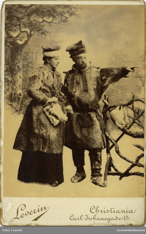 Studiefotografi av Distriktslege Andreas Bredal Wessel og hans kone Ellisif Wessel ikledd pesk, skaller og stjernelue foran et tregjerde.