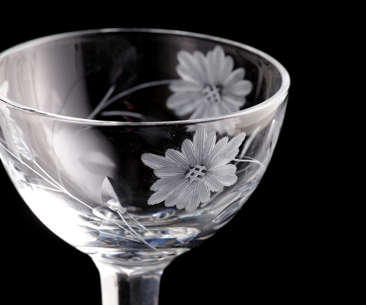 """Rundad kupa med tre slipade blommor. Facettslipat ben. Kronbladen är schattérslipade och bladen är skärslipade. Etikett: Rektangulär med blå botten. En vit ring med ett """"B"""" texten """"Bergdala Sweden"""", sam tsvenska flaggan."""